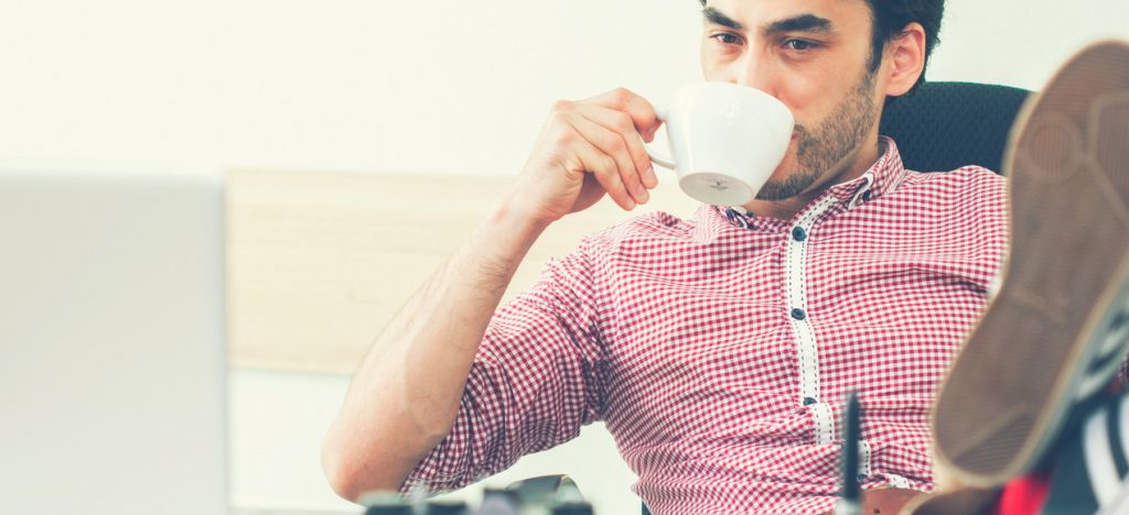 A man working at his desk with a cup of coffee.