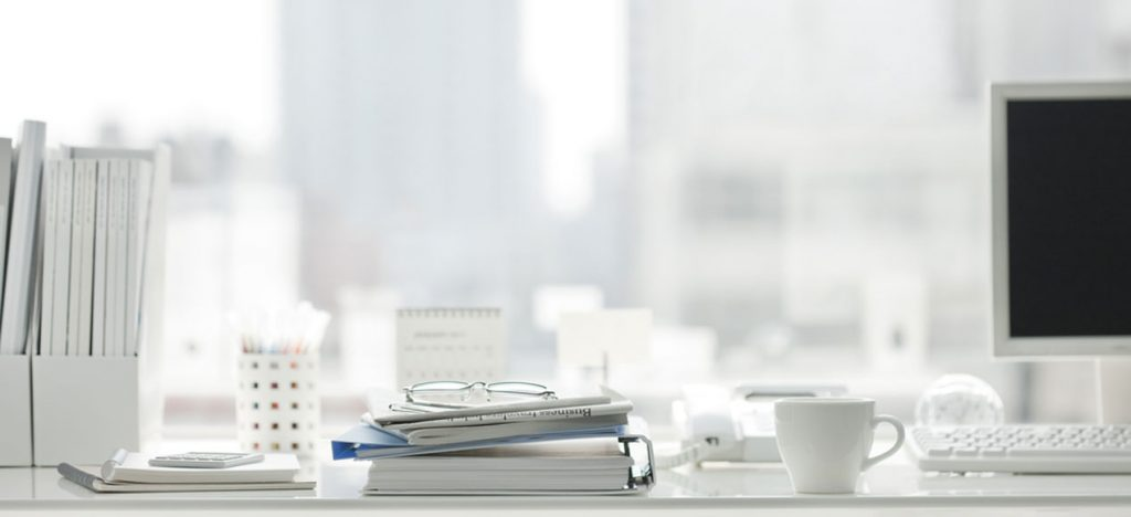 Photo of a desk and city view in tones of white.