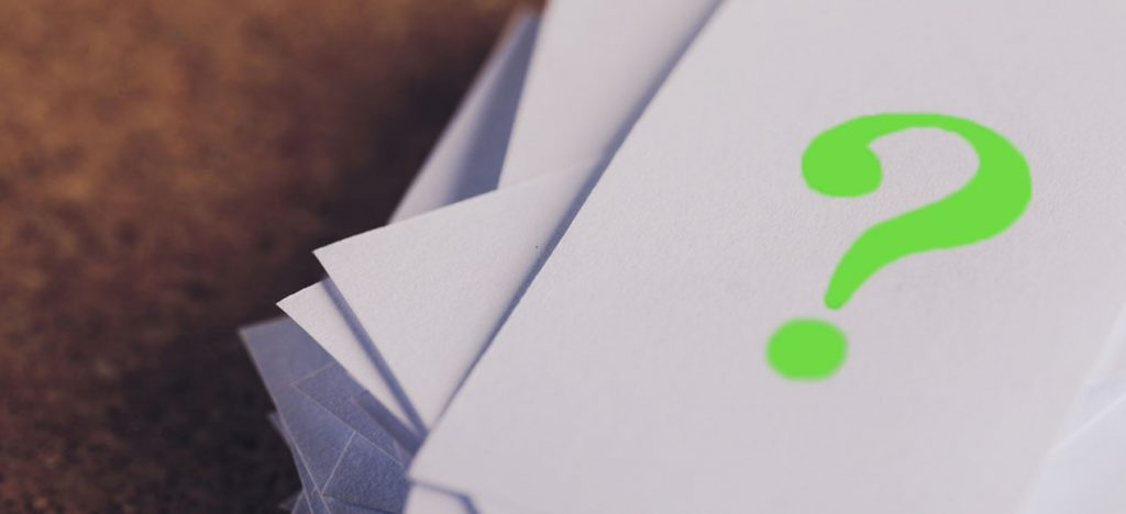 A stack of paperwork, topped with a green question mark.