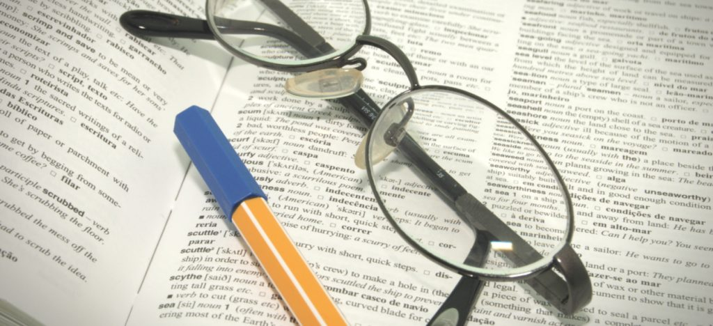dictionary with glasses and pencil