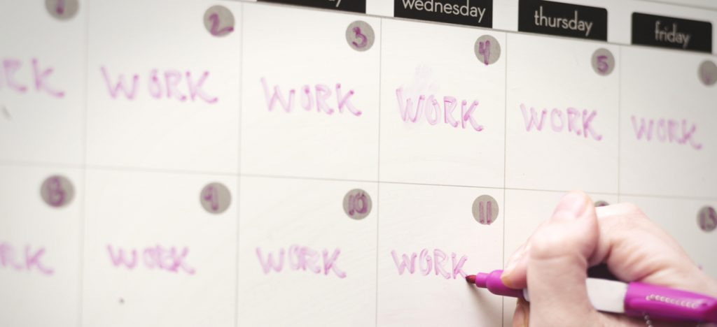 person filling up whiteboard calendar with word work