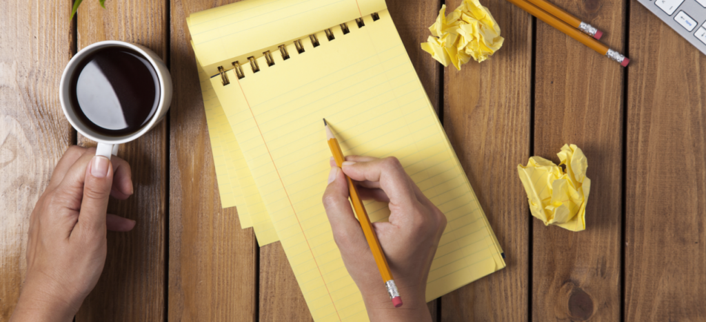 person outlining on a yellow pad